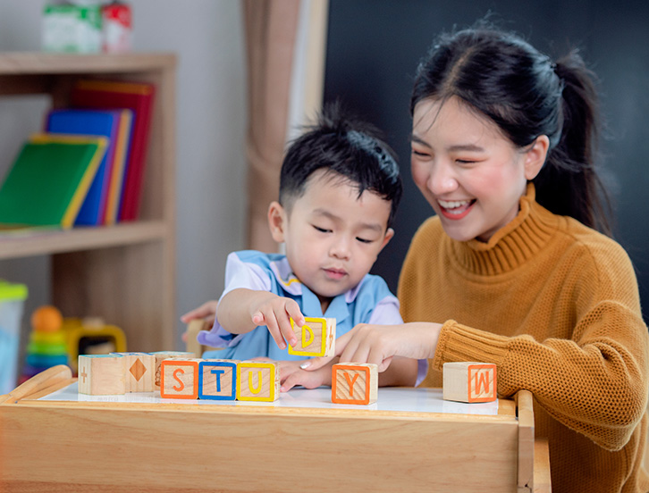 child and caretaker playing with blocks