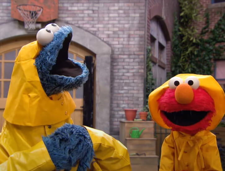 Cookie Monster and Elmo in rain gear