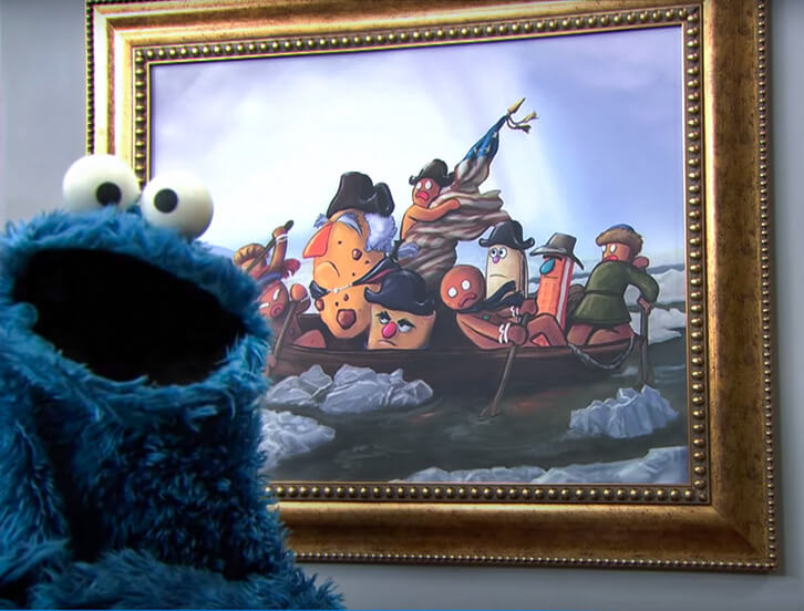 Cookie Monster posing next to art