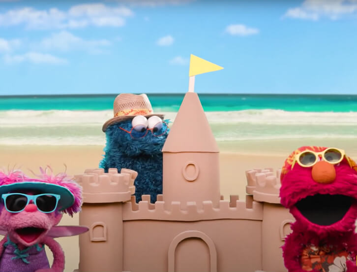 Abby, Cookie Monster and Elmo building a sand castle